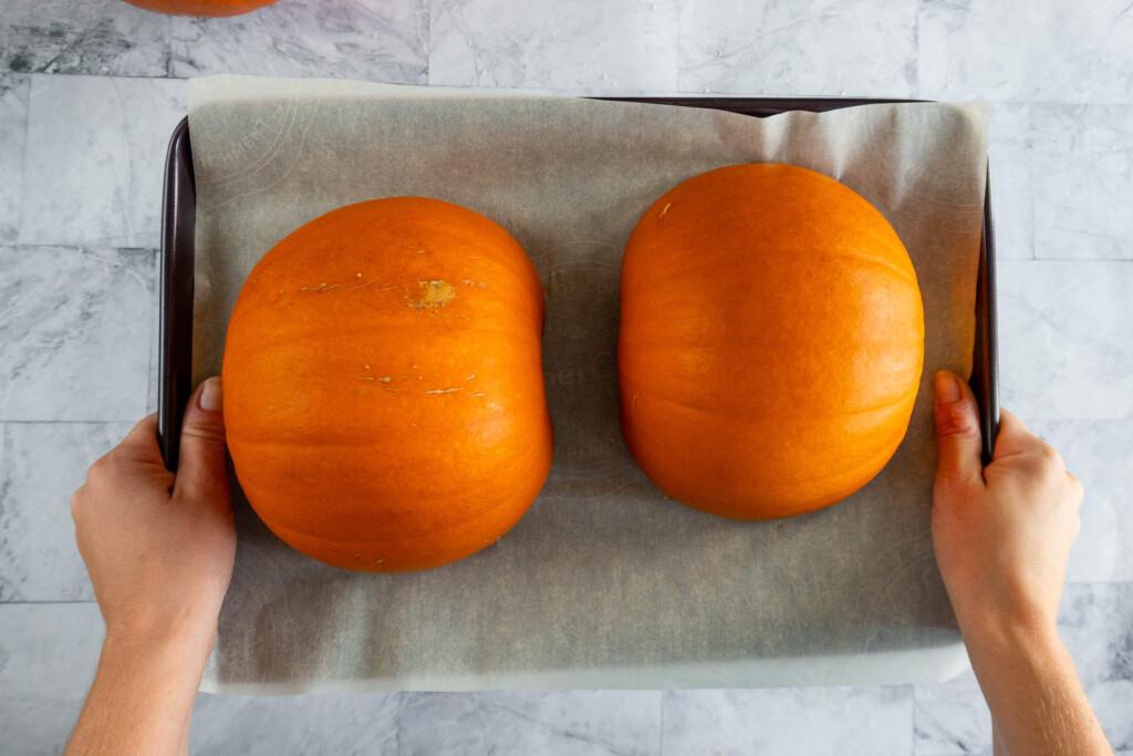 Two pumpkin halves face down on a baking sheet.