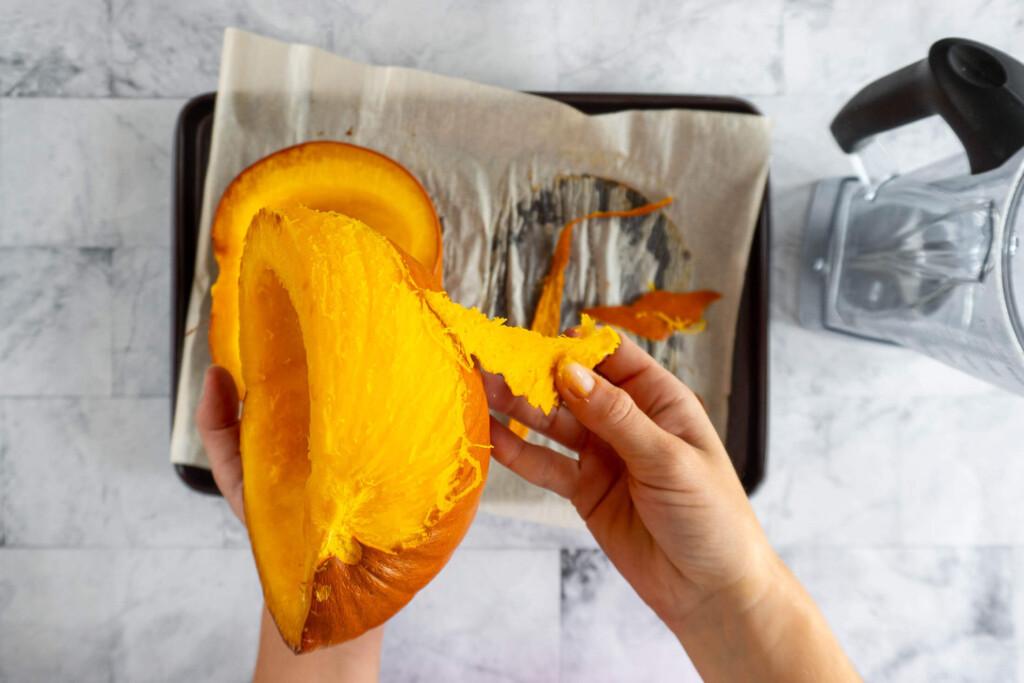 Peeling pumpkin skin off the cooked pumpkin.