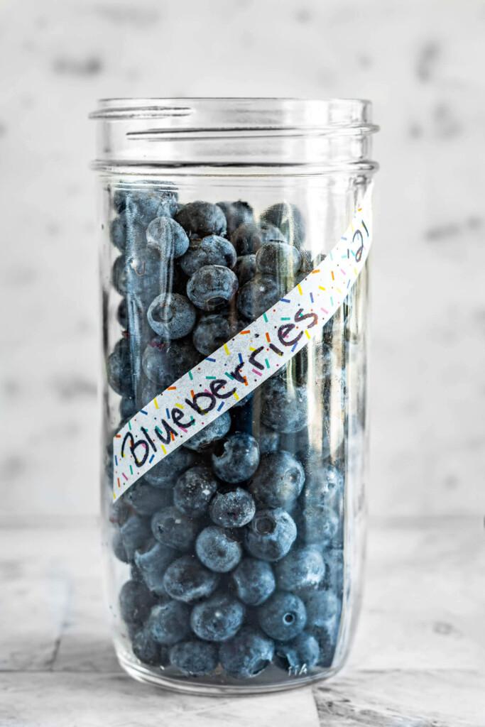 Frozen blueberries in a tall mason jar.