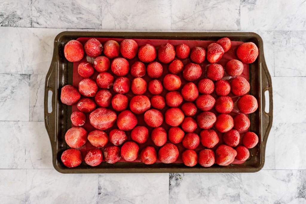 Frozen strawberries on a baking sheet.