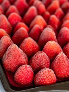Frozen whole strawberries on a baking sheet.
