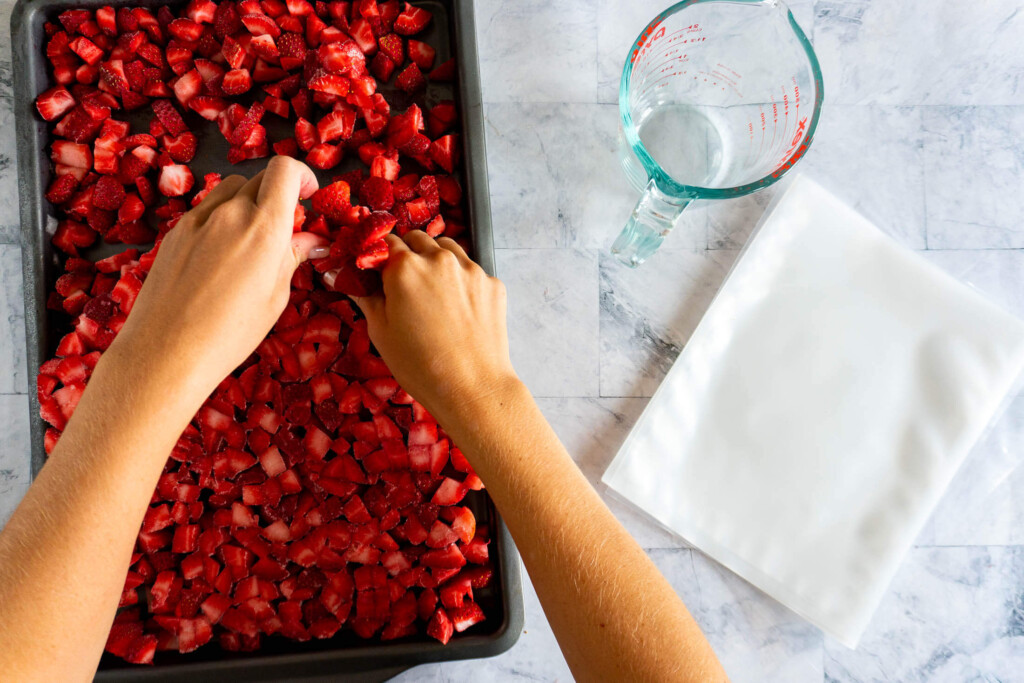 Breaking apart the frozen strawberry pieces.