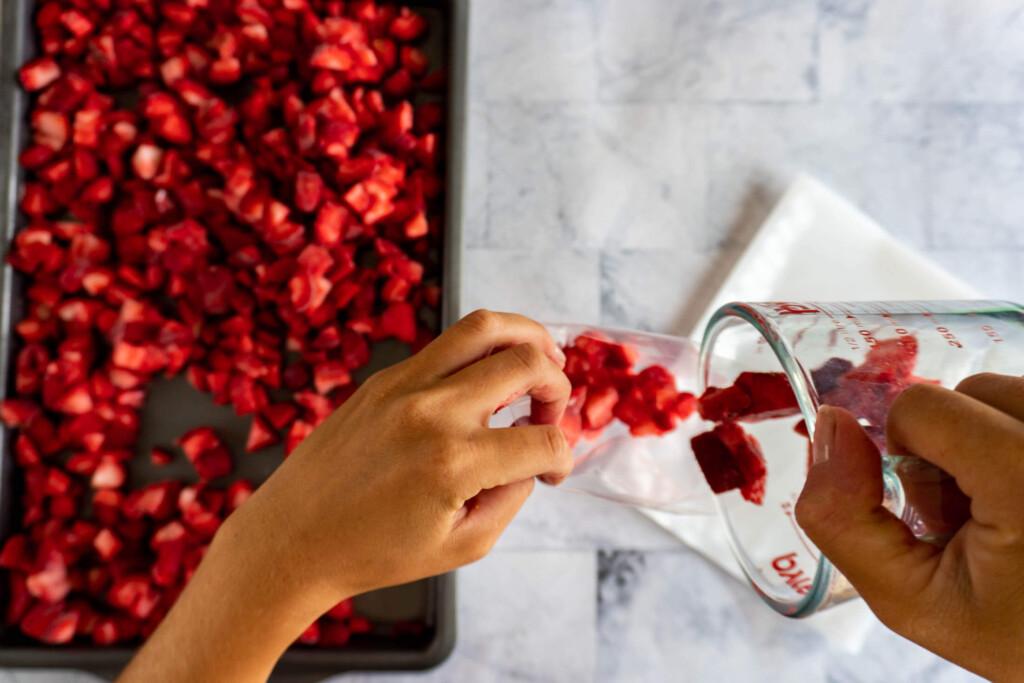 Transferring pre-measured quantities of berries to a vacuum seal bag.