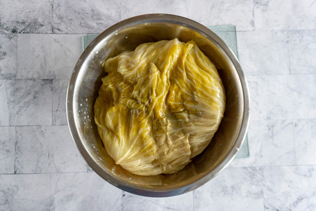 A fully soured head of cabbage in a large bowl.