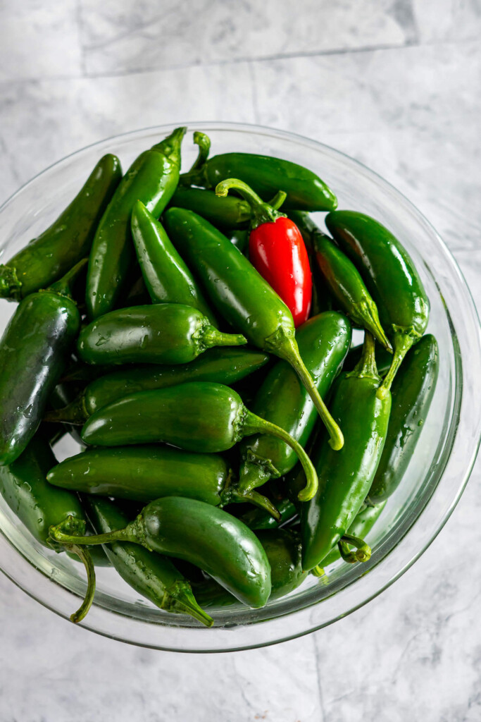 A glass bowl overflowing with jalapenos.