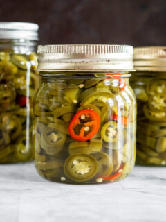A jar of pickled jalapenos with a ring from one red jalapeno.