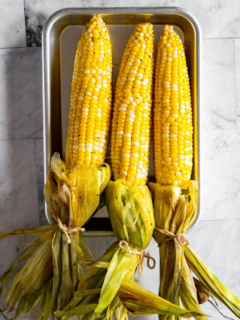 Smoked corn on the cob on a tray.
