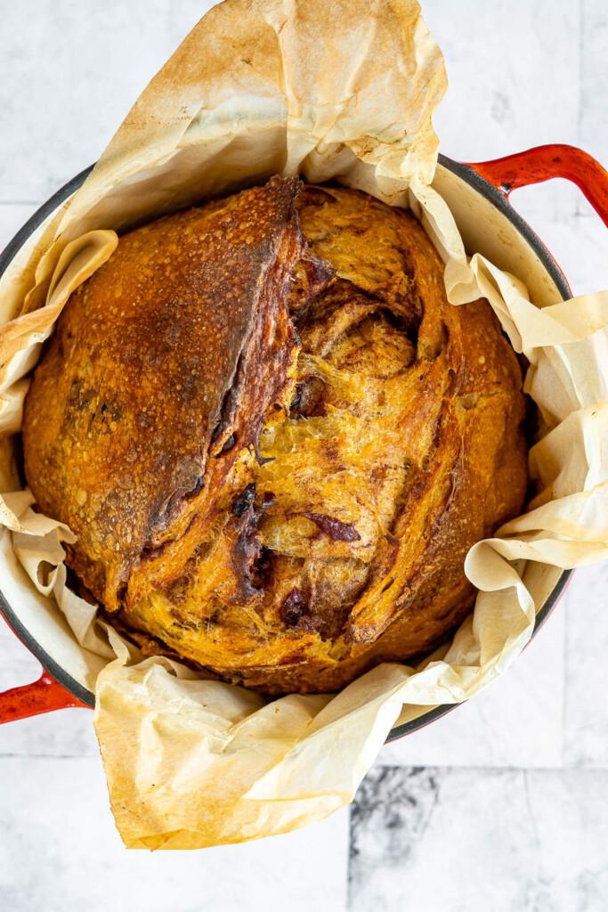 Overhead view of baked pumpkin sourdough bread in a dutch oven.