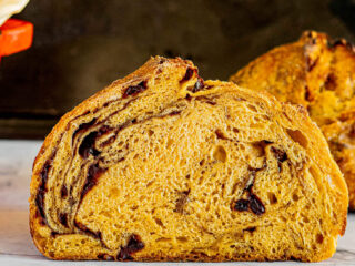A sliced loaf of pumpkin sourdough bread.